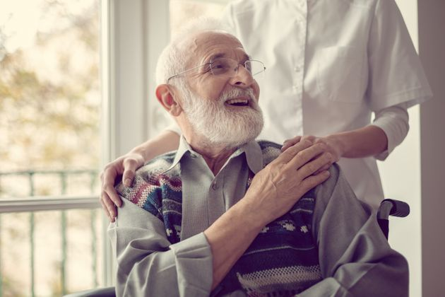 Senior man sitting on the wheelchair, laughing and holding his nurse's