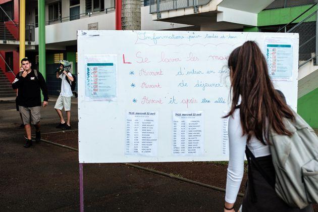 Une élève lit les instructions sanitaires au lycée Lapérouse à Nouméa,...