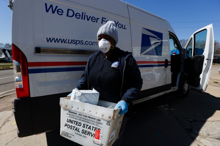 A United States Postal worker makes a delivery with gloves and a mask in Warren, Michigan, earlier this month.
