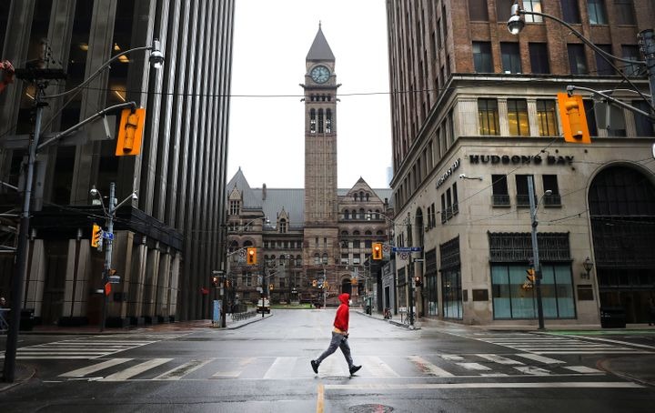 A man runs across an empty intersection in Toronto. After weeks of practicing social distancing, Canadians are wondering when life will return to normal.