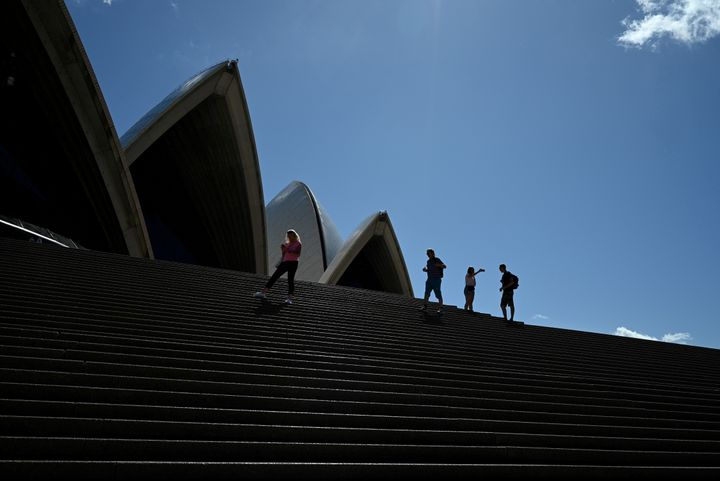A handful of tourists stand atop the mostly deserted steps of the Sydney Opera House, where scheduled public performances hav