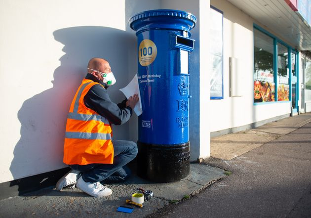 A man preopares a letter box painted blue to mark the 100th birthday of Second World War veteran Captain...