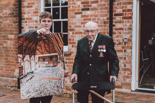 Benjie Ingram-Moore presenting his grandfather Captain Tom Moore with a photograph of the Great Hall...