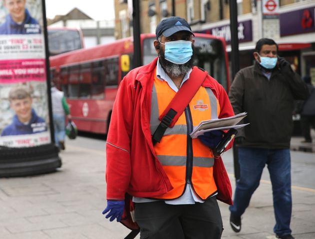 A postman wearing protective personal equipment walks through East Ham, east