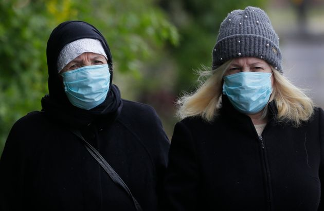 People wear face masks to protect against the coronavirus as they walk in