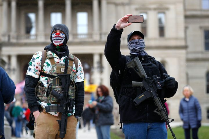 Protesters with rifles stand outside the state Capitol in Lansing, Michigan, on April 15 to demonstrate against Gov. Gretchen