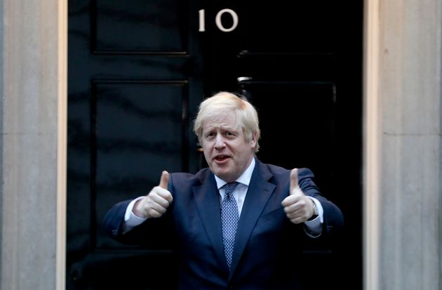 Boris Johnson shows thumbs up before he applauds on the doorstep of 10 Downing Street in London during...