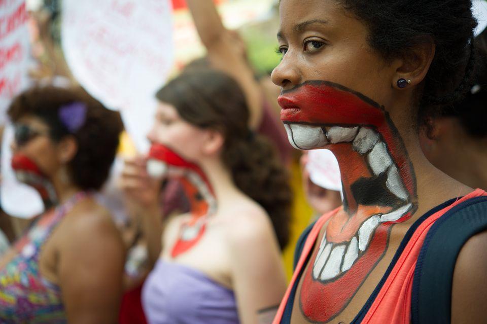 Mulheres marcham com bocas pintadas no rosto e pescoço - para chamar a atenção para...