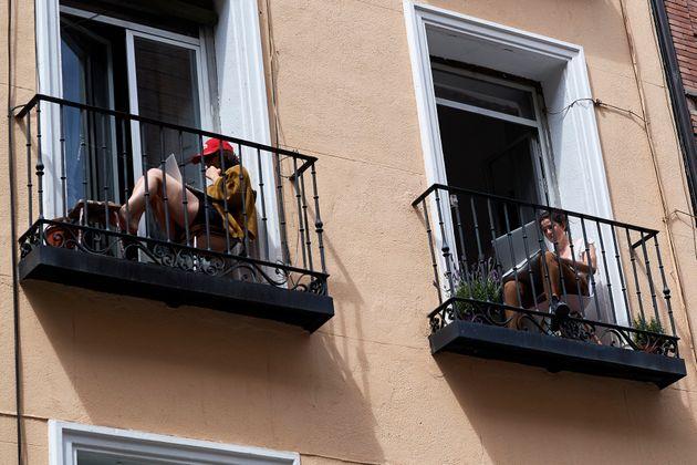 Dos mujeres trabajan con sus portátiles en balcones de