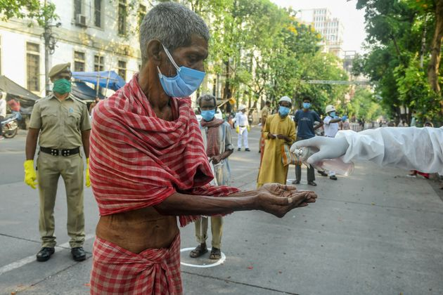 A slum dweller in Kolkata cleans his hands with sanitizer before collecting relief material on April...