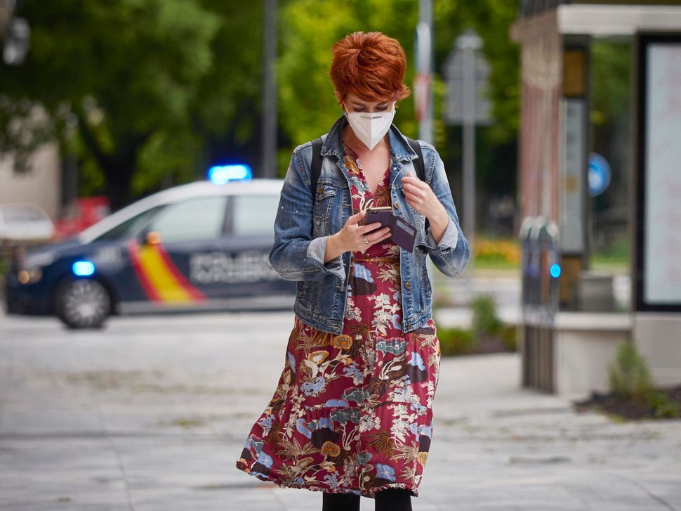 A woman wearing a mask looks at her phone on April 30 in Pamplona, Spain. The Spanish government has unveiled its plan for ea