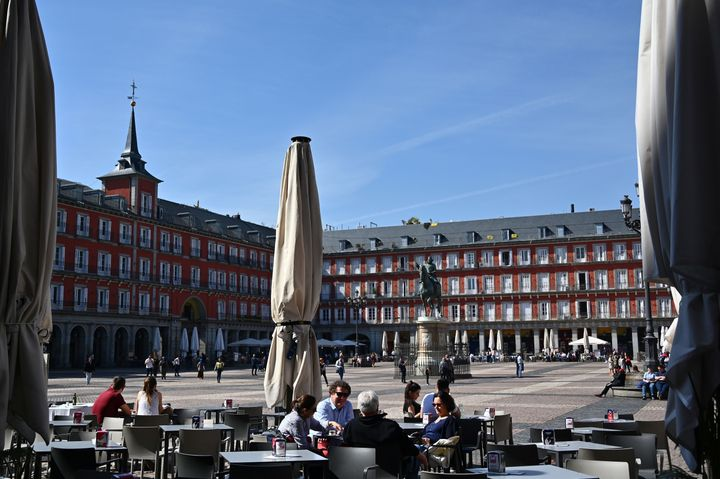 People sit at a terrace at Madrid's Plaza Mayor on March 13 as the city's mayor announced that he would order the closure of all outdoor bar and restaurant terraces. Under Spain's plan to ease lockdown restrictions, sidewalk cafes will be allowed to reopen with limited capacity.