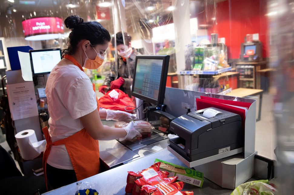 A cashier wearing a mask and gloves stands behind plastic sheeting at a supermarket in Paris on April 8. Such protective meas