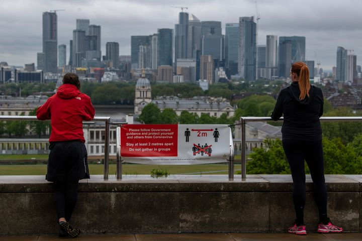 Joggers stop to look at the London skyline from Greenwich Park on April 28. Social distancing measures are likely to become a standard part of life for the foreseeable future.
