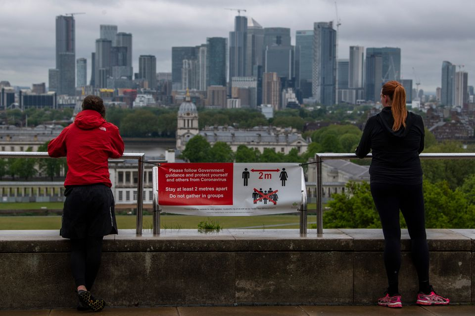 Joggers stop to look at the London skyline from Greenwich Park on April 28. Social distancing measures...