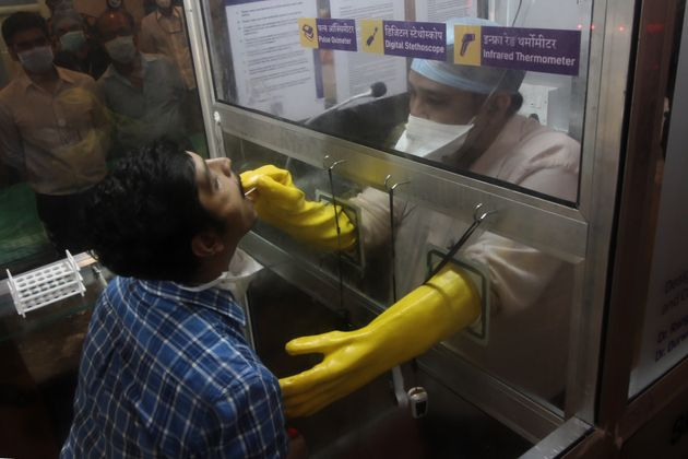 An instructor collects swab samples from a person during an inauguration of Smart Covid-19 OPD at JJ...