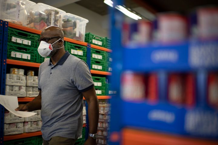 First Love foundation food bank co-founder, Aerold Bentley walks past goods for distribution to families, at the First Love foundation foodbank warehouse in Tower Hamlets.