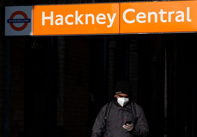 A man in a face mask leaves Hackney Central