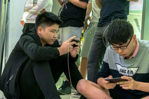 スマホゲームで対戦する中国の若者