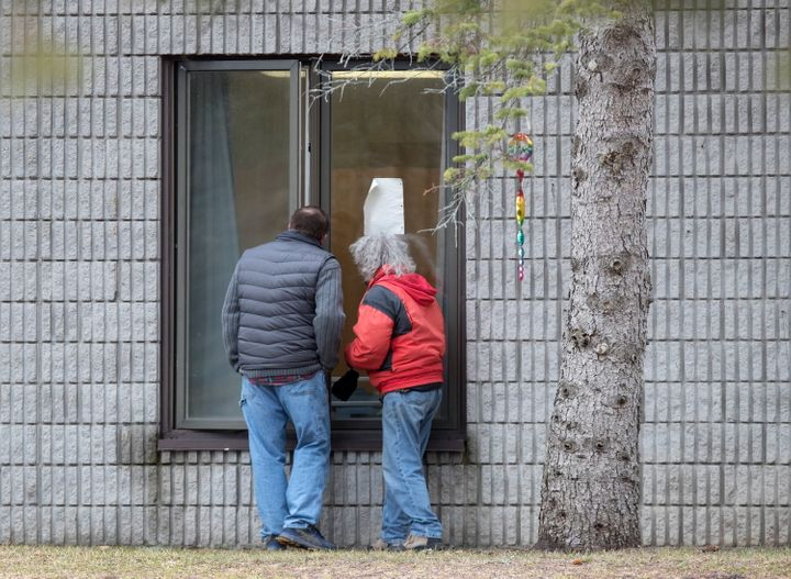 Visitors visit residents through a window at Pinecrest Nursing Home on March 30 in Bobcaygeon, Ont.
