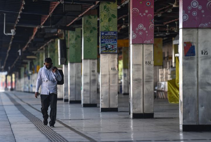 A man walks down an empty railway platform during the nationwide lockdown at Anand Vihar Terminal railway station on April 25, 2020 in New Delhi.