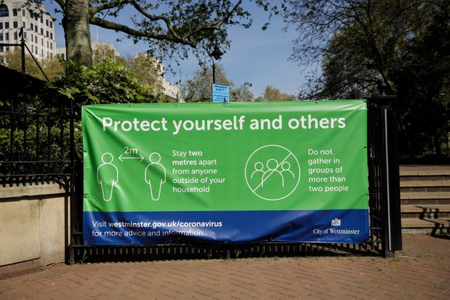 A coronavirus guidelines banner is displayed by an entrance to Victoria Embankment Gardens in