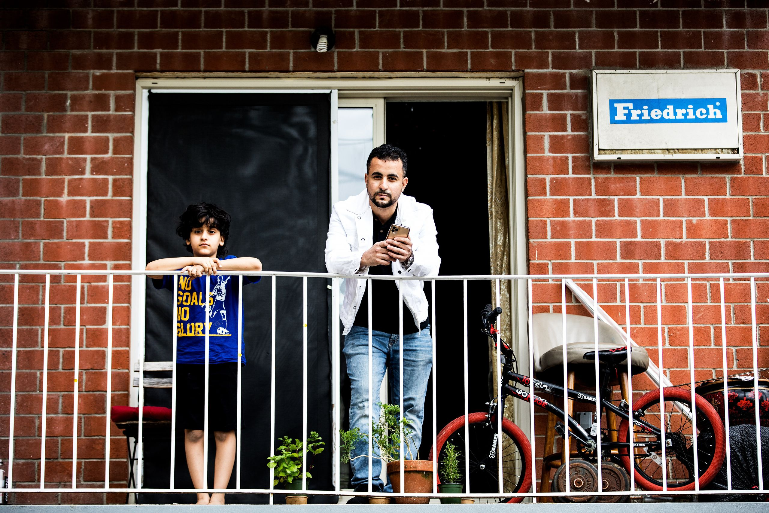 Abdullah, Emad Al-Azabi's cousin, stands with his nephew on the balcony of his home in Queens, New York City, in April.
