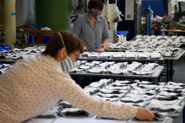 Des employés préparant des masques en tissu à l'usine de vêtements
