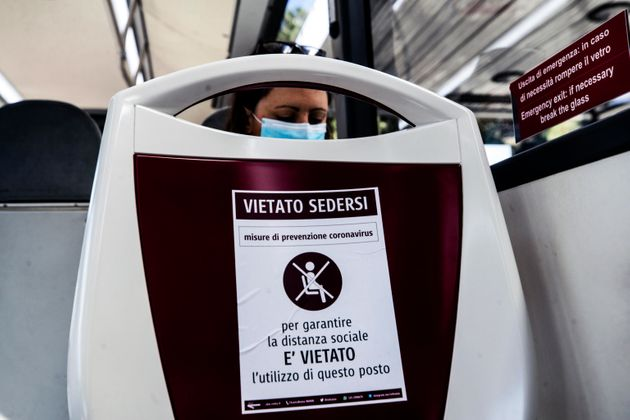 Prohibition signs to sit for the social distancing of passengers installed on public bus seats during...