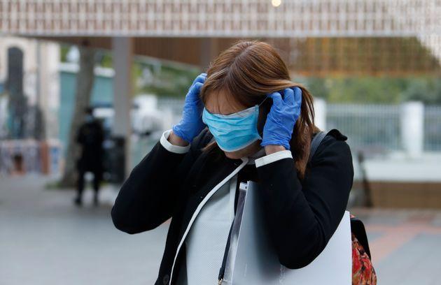 Una mujer trata de colocarse una mascarilla, en