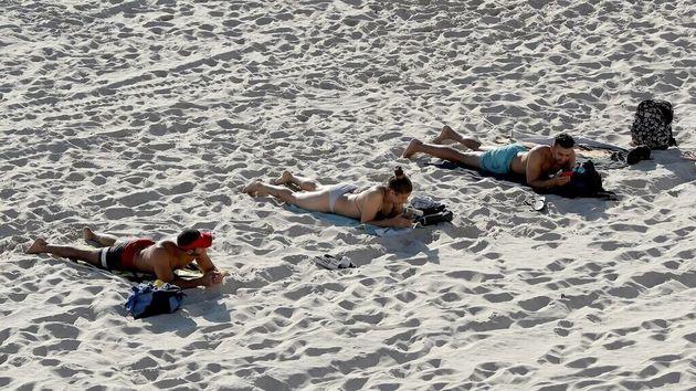 Personas en la playa guardando la distancia de