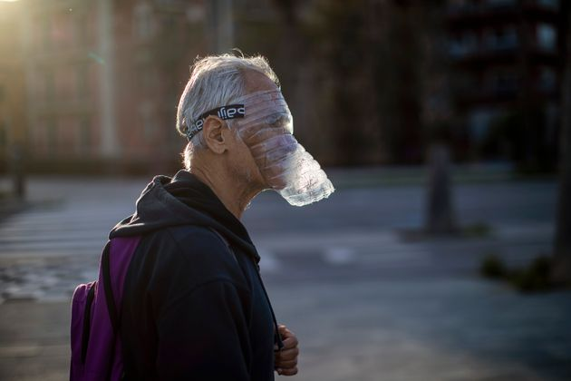 A man uses a plastic bottle as a face mask as he walks in a seafront promenade during sunset in Barcelona,...