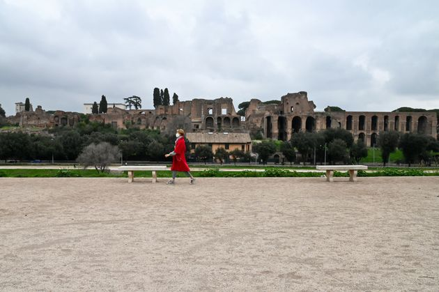 A person wearing a respiratory mask walks across a deserted Circo Massimo in front of Palatine Hill,...