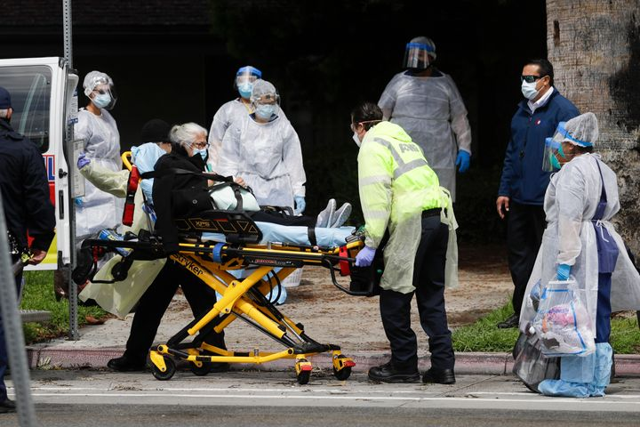 A patient is evacuated from the Magnolia Rehabilitation and Nursing Center in Riverside, Calif., Wednesday, April 8, 2020. (A