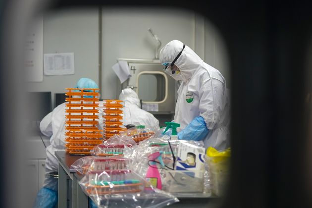 Photo shows medical workers in protective suits at a coronavirus detection lab in Wuhan in central China's...