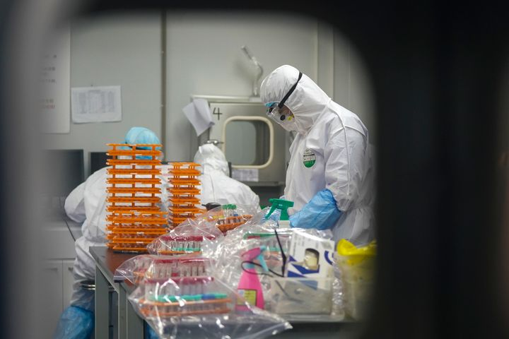 Photo shows medical workers in protective suits at a coronavirus detection lab in Wuhan in central China's Hubei Province. (Cheng Min/Xinhua via AP)