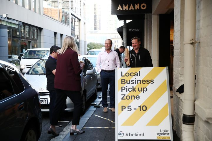 Customers wait for their coffee, bread and pastries outside Amano Bakery on April 29, 2020 in Auckland, New Zealand. With COVID-19 lockdown measures easing slightly, restaurants and other food providers are adapting their operations to be able to trade again. (Photo by Fiona Goodall/Getty Images)