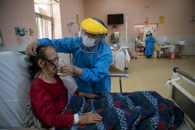 A nurse places an oxygen mask on a patient inside the intensive care unit for people infected with the...