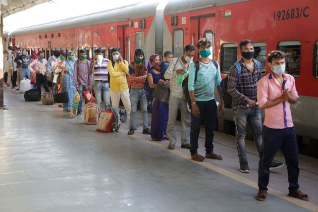 Migrant workers stand in a queue to board a special train to return to Agra in Uttar Pradesh on Saturday,...