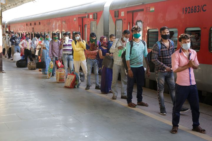 Migrant workers stand in a queue to board a special train to return to Agra in Uttar Pradesh on Saturday, May 2, 2020.