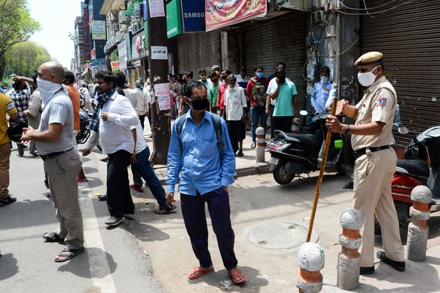 Police disperse people lining up to buy alcohol near a liquor shop in New Delhi on May 4,