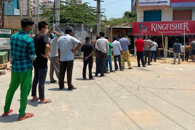 People queue at a liquor store in Bangalore on May 4,