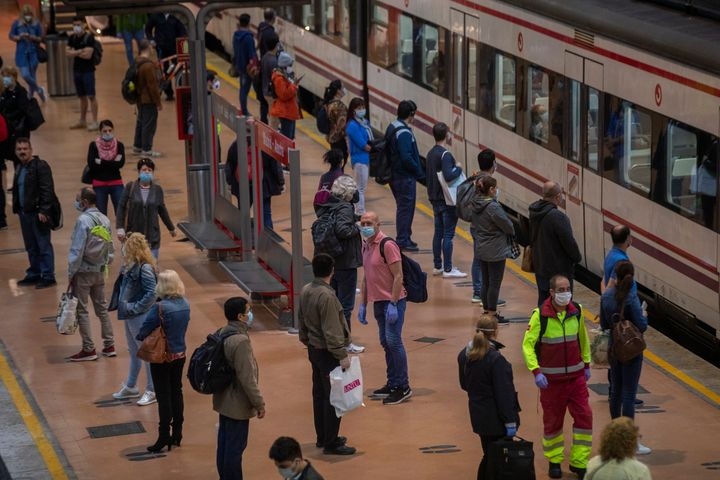 Commuters wearing face masks to protect against coronavirus stand on the platform at Atocha train station in Madrid.