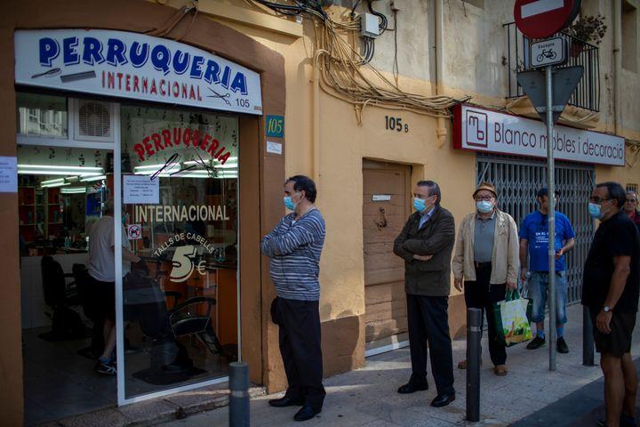 Men line up at a barber's in Barcelona.