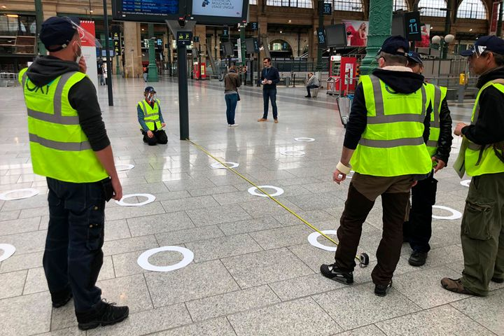 Workers measure the distance between circles to help passengers at Paris' Gare du Nord train station maintain social distanci