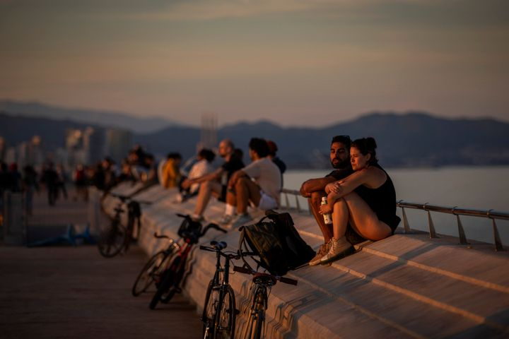 People sit on a seafront promenade during a sunset in Barcelona.