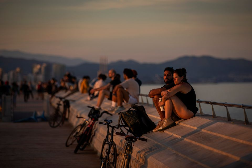 People sit on a seafront promenade during a sunset in