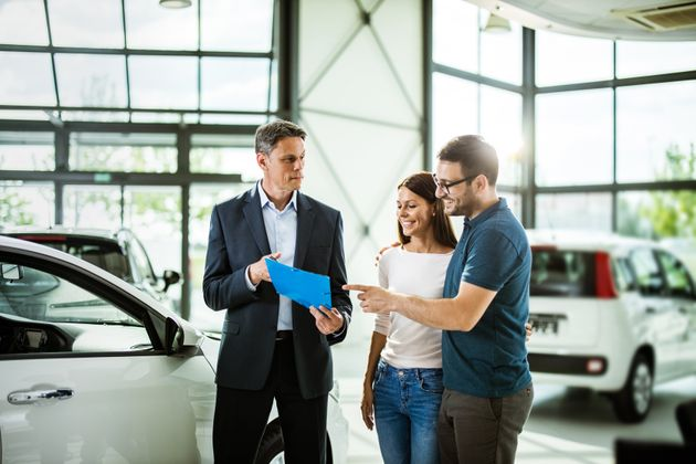 Happy couple reading buying plan with car salesperson in a