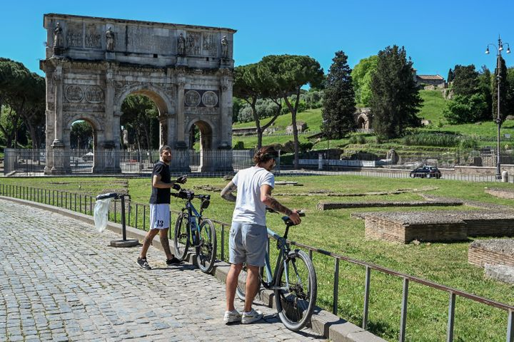 Cyclists park their bikes near the Arch of Constantine monument in central Rome.