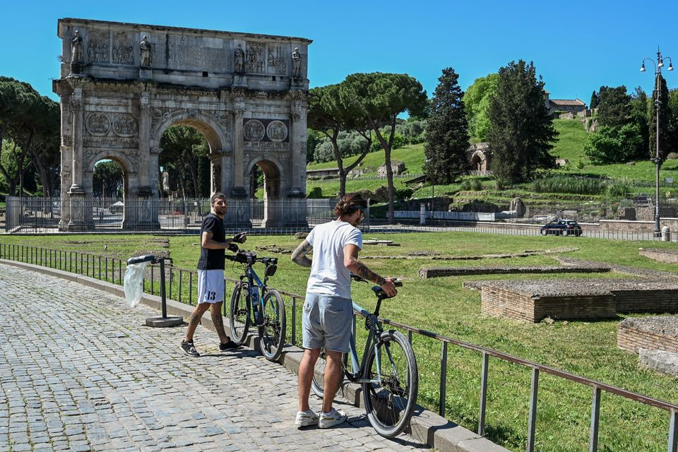 Cyclists park their bikes near the Arch of Constantine monument in central